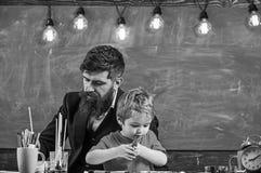 Kind en leraar die op bezige gezichten, het trekken schilderen Leraar met baard, vader en weinig zoon in klaslokaal terwijl het t stock afbeelding