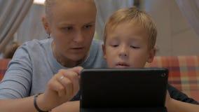 Kind en mamma met digitale tablet in koffie stock video