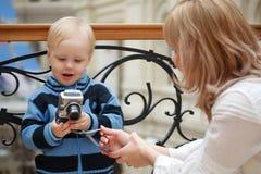 Kind en moeder. De jongen onderzoekt foto met camera Stock Afbeelding