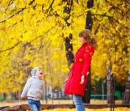 Kind en moeder met de herfstbladeren Royalty-vrije Stock Afbeeldingen