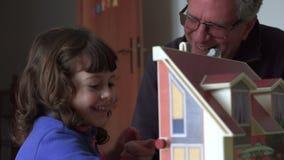 Kind en papa het spelen met poppenhuis en lach SF stock video