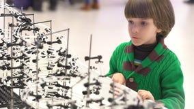 Kind en robot: een nieuwsgierige jongen bij een tentoonstelling van robots Modern speelgoed Kinderen en de toekomst Virtuele Spel stock video