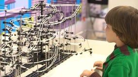 Kind en robot: een nieuwsgierige jongen bij een tentoonstelling van robots Modern speelgoed Kinderen en de toekomst Virtuele Spel stock footage