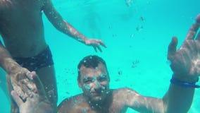 Kind en vader golvende handen wanneer het duiken in de pool stock videobeelden