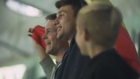 Kind en volwassen Spaanse voetbalventilators die vlag golven, die volkslied zingen stock video