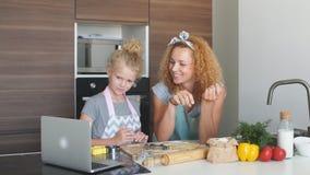 Kind en vrouwen die vorm voor koekje in deeg snijden Gelukkige familie en kinderjaren stock footage