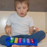 Kind en xylofoon De jongen klopt zijn eetstokjes op xyloph royalty-vrije stock foto