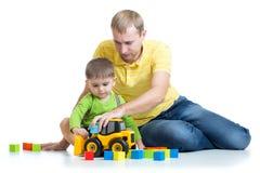 Kind en zijn het stuk speelgoed van de papareparatie tractor Royalty-vrije Stock Afbeelding