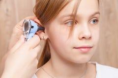 Kind ENT controle - arts die oor van elementaire wi van het leeftijdsmeisje onderzoeken royalty-vrije stock fotografie
