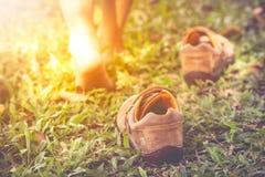 Kind entfernen Schuhe Kind-` s Fuß lernt, auf Gras mit zu gehen Lizenzfreies Stockfoto