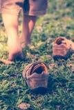 Kind entfernen Schuhe Kind-` s Fuß lernt, auf grünes Gras zu gehen Stockfotografie