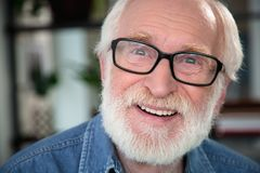 Kind excited bearded man smiling at camera. Sincere gladness. Close up portrait of happy pensioner expressing delight and openness Stock Photography