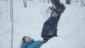 Kind fällt in den Schnee in der Zeitlupe Aktiver Sport draußen Sonniger Tag des Winters stock footage