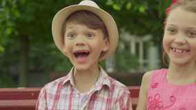Kind för ` s för liten flickakysspojke på bänken arkivfilmer