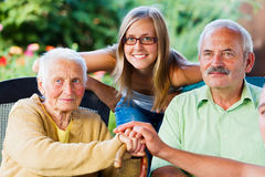 Kind Family Visiting Elderly Lady Stock Photo