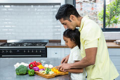 Kind father helping his daughter slicing vegetables Royalty Free Stock Photo
