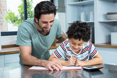 Kind father helping his son doing homework. In the kitchen stock photo