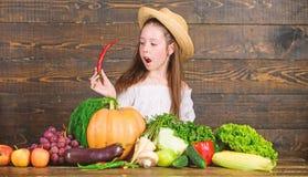 Kind feiern das Ernten M?dchenkinderbauernhofmarkt mit Fallernte Kinderlandwirt mit h?lzernem Hintergrund der Ernte familie stockfotos