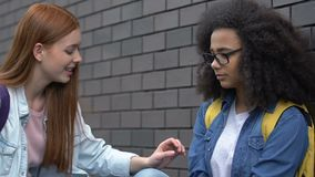 Kind female student giving helping hand to bullied biracial girl, stop racism. Stock footage stock footage