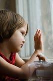 Kind am Fenster an einem regnerischen Tag Stockbilder