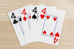 4 of a kind fours 4 - casino playing poker cards. 4 of a kind fours 4  - winning hand of gambling casino poker playing cards on a table royalty free stock photography