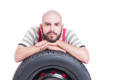 Kind and friendly young mechanic resting on car wheel tire Royalty Free Stock Image