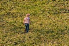 Kind geht über die Wiese Stockfotografie