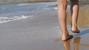 Kind geht entlang die Brandung Die Füße der Kinder auf dem Hintergrund von Wellen Meerwasser wäscht weg den Abdruck stock footage