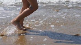 Kind geht entlang die Brandung Die Füße der Kinder auf dem Hintergrund von Wellen Meerwasser wäscht weg den Abdruck stock video