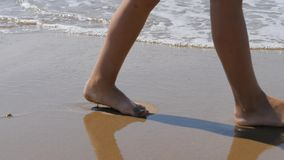 Kind geht entlang die Brandung Die Füße der Kinder auf dem Hintergrund von Wellen Meerwasser wäscht weg den Abdruck stock video footage
