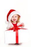 Kind gekleidet als Sankt mit einem Weihnachtsgeschenk Lizenzfreies Stockbild