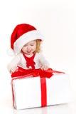 Kind gekleidet als Sankt mit einem Weihnachtsgeschenk Lizenzfreie Stockfotos