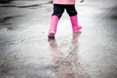 Kind gekleidet in der rosa Kleidung, die in Pf?tzen springt lizenzfreie stockfotos