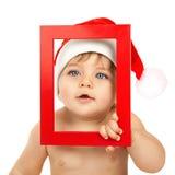Kind gekleidet im roten Weihnachtshut Lizenzfreies Stockfoto