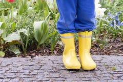 Kind in gele rubberlaarzen in tuin royalty-vrije stock foto