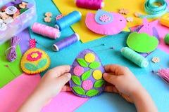 Kind gemaakt paaseidecor van gevoeld Het kleine kind houdt een gevoeld paaseidecor in zijn handen Pasen-geplaatste ambachten Royalty-vrije Stock Afbeelding