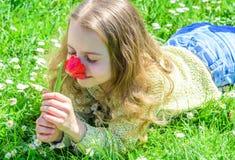 Kind genießen Duft der Tulpe beim Lügen an der Wiese Allergiekonzept Mädchen auf glücklichem Gesicht hält rote Tulpenblume an lizenzfreies stockfoto