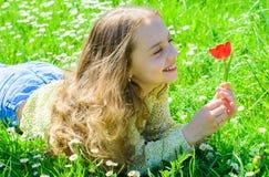 Kind genießen Duft der Tulpe beim Lügen an der Wiese Mädchen mit dem langen Haar, das auf grassplot, Grashintergrund liegt allerg stockbilder