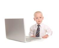 Kind-Geschäftsmann, der an einer Laptop-Computer arbeitet stockfotografie