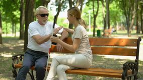 Kind girl helping blind pensioner to sit on bench, respect and care for disabled stock video footage