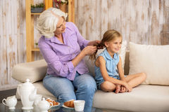 Kind grandmother braiding childish hair Royalty Free Stock Photography
