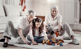 Kind grandparents recreate with focused granddaughter. Repeat after me. Warmhearted beaming grandparents sitting on the carpet playing with lego while royalty free stock photos