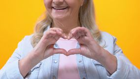 Kind granny making heart sign by hands, love symbol, romantic gesture, flirt. Stock footage stock video footage
