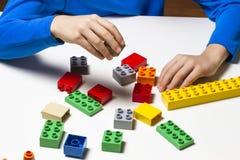 Kind hält Bausteine in seinen Händen und Spiel im Kindergarten oder zu Hause Stockbilder