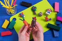 Kind hält in der Hand Karotte und Maus von Plasticine Stockbild