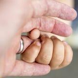 Kind hält ein ringfinger seines Vaters Stockbild