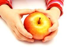 Kind hält frischen Apfel an Stockbild