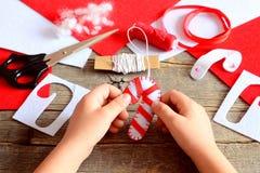 Kind hält Weihnachtsfilz-Zuckerstange in seinen Händen Materialien und Werkzeuge, zum von Weihnachtsbaumdekorationen herzustellen Stockbilder