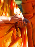 Kind Hands. Clasped hands of Buddhist monk in traditional garb royalty free stock photo