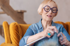 Kind-hearted old woman knitting scarf Stock Image